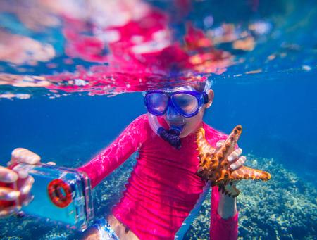 estrella de mar: foto autofoto bajo el agua de una niña feliz con una estrella de mar gigante Foto de archivo