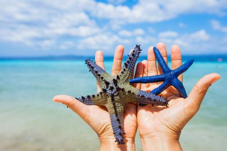 Zwei schöne bunte Seesterne in Mädchen die Hände in den blauen hellen Sommer Wasser.