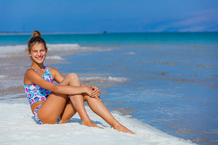 Beautiful girl relaxing on the shore of the Dead Sea Imagens - 56797854
