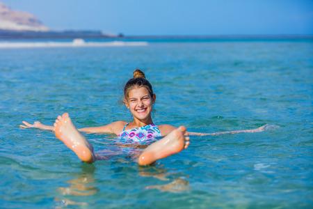 Schönes Mädchen in den Gewässern des Toten Meeres, Israel schwimmend