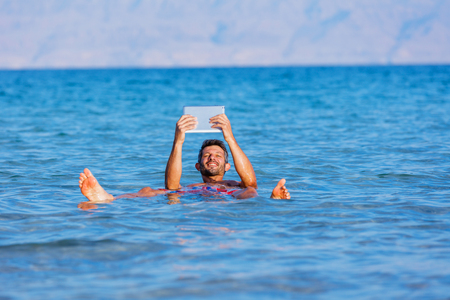 Man floating with the tablet in the waters of the Dead Sea, Israel
