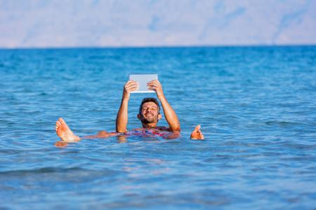 Man schwimmend mit dem Tablett in den Gewässern des Toten Meeres, Israel Standard-Bild