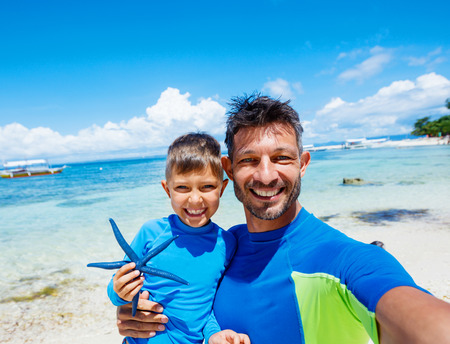only man: Boy with his father holding a blue starfish on sandy beach, Philippines