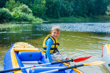 adventurous: Active happy child having fun adventurous experience kayaking on the river on a sunny day during summer vacation