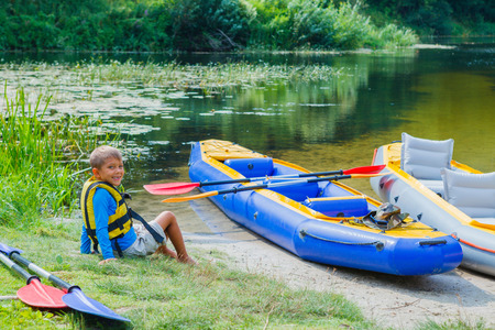 adventurous: Active boy resting after adventurous experience kayaking on the river on a sunny day during summer vacation Stock Photo