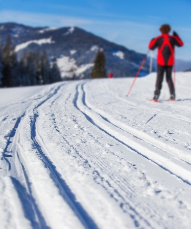crosscountry: Cross-country skiing in Alps. Man cross-country skiing on a lovely sunny winter day. Focus on the ski run