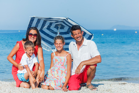 holidaying: Happy family holidaying on a sandy beach Stock Photo