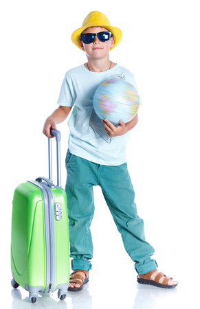 schooler: Happy boy in hat and sunglasses traveling with suitcase. Isolated on the white background