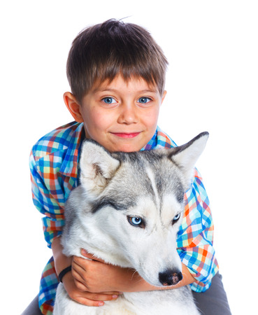 affectionate action: Cute boy with his dog husky isolated on white background Stock Photo