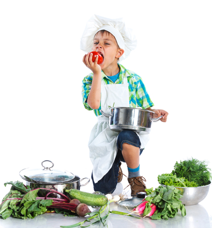 preschooler: Cute boy in chefs hat with big ladle, casserole, and fresh vegetables over white background Stock Photo