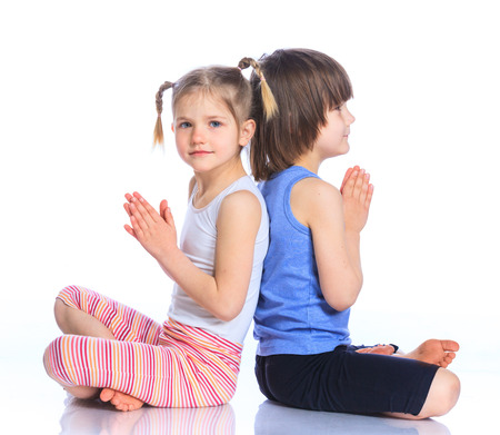 pleasantness: Cute little boy and girl practice yoga. Isolated on the white background