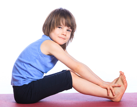 pleasantness: Cute little boy practice yoga. Isolated on the white background