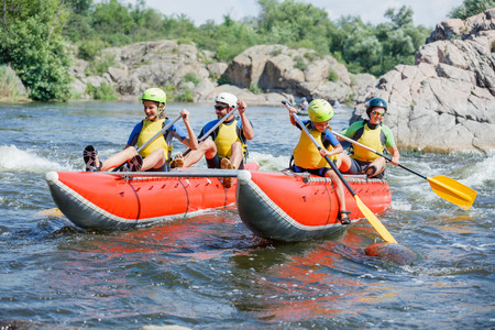 river rafting: Yappy family of four river rafting on the catamaran Stock Photo