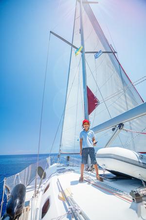 Weinig jongenskapitein aan boord van zeiljacht op de zomercruise. Reisavontuur, zeilen met kind op familievakantie.