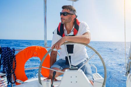 Young man sailing yacht