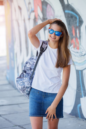 clothing store: Girl wearing blank white t-shirt, jeans posing against rough street wall