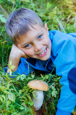 Boy with wild mushroom found in the forest