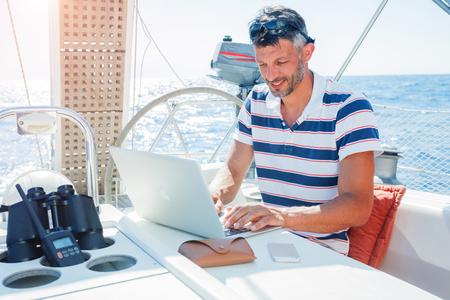 Man with laptop computer on sailboat Foto de archivo
