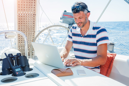 Man with laptop computer on sailboat Standard-Bild