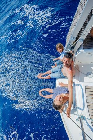 ヨットの上で休んでいる愛らしい子供と父親
