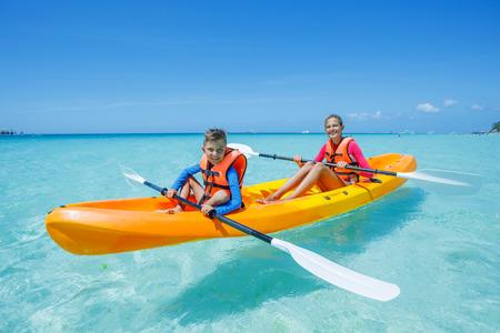 niño sin camisa: Dos chirdren kayak en el mar tropical en kayak amarillo