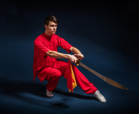 Boy in a red kimono engaged wushu