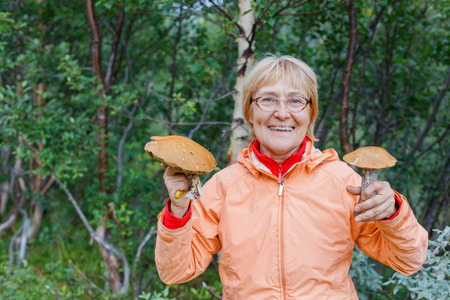 Active older woman - mushroom picker, inhale the smell of white mushrooms found it.