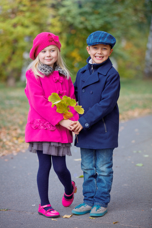Children walking in beautiful autumn park on warm sunny fall day.