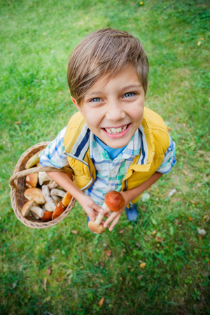 Cute boy with wild mushroom found in the forest