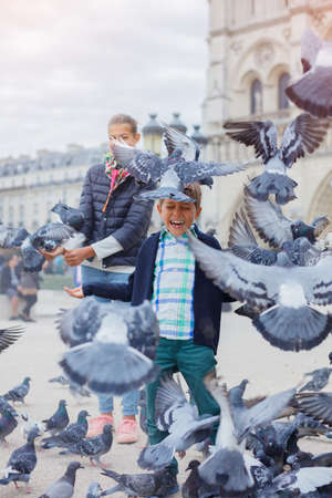 voyage: Boy with his sister birds near Notre Dame de Paris cathedral in Paris, France