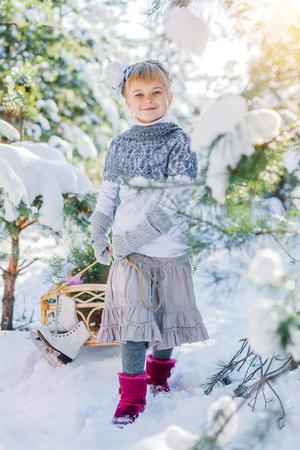 newyear: Winter fairy tale. Beautiful little girl is walking in a snowy forest