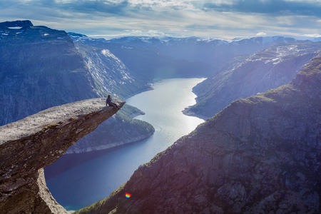 Man sitting on trolltunga in norway Фото со стока