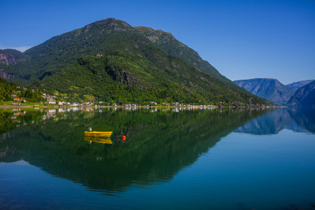Fishing boat sailing on water with mountains in Norway.