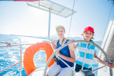 Boy captain with his sister on board of sailing yacht on summer cruise. Travel adventure, yachting with child on family vacation. Stock Photo