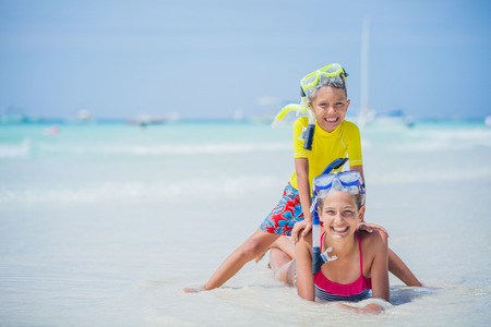 Brother and sister in scuba masks playing on the beach during the hot summer vacation day.