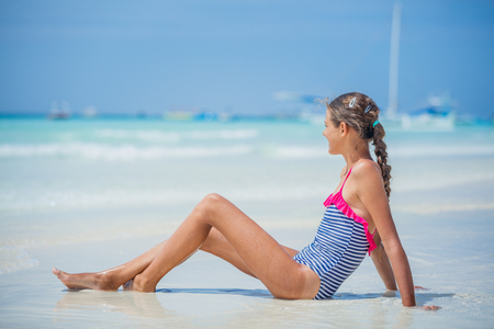 Girl in bikini lying and having fun on tropical beach