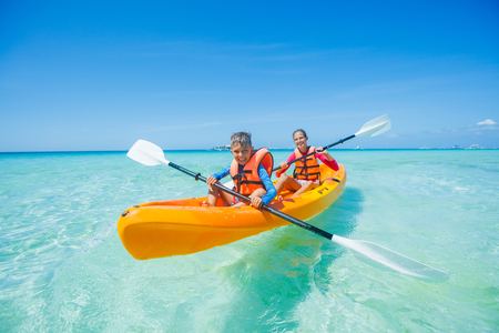 Happy boy and girl kayaking at tropical sea on yellow kayak