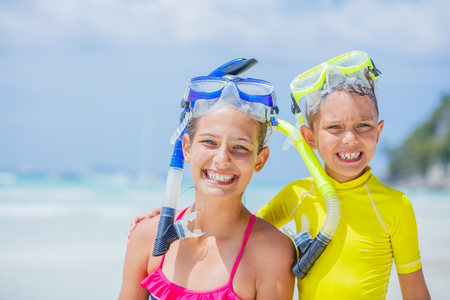 Portrait of Brother and sister in scuba masks playing on the beach during the hot summer vacation day.