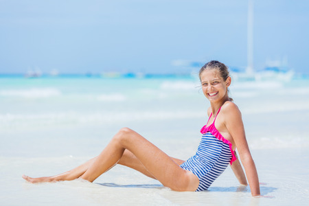Girl in swimsuit sitting and having fun on tropical beach