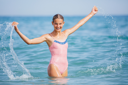 Girl in swimsuit having fun on tropical beach Banque d'images