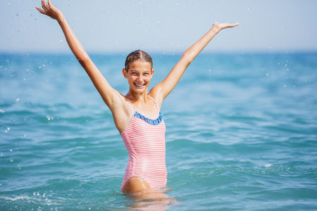 Girl in swimsuit having fun on tropical beach Stock Photo