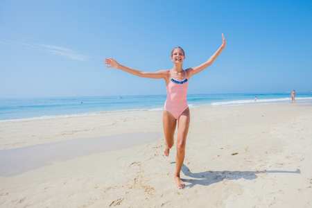 Girl in swimsuit runing and having fun on tropical beach Banque d'images