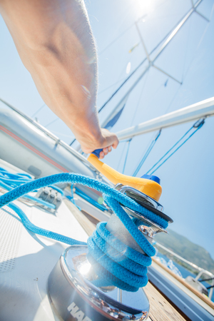 Hand of captain sail boat working on the boat with Winch on a sailboat. Yacht tackle during the ocean voyage, sailing concept. Outdoors horizontal colored closeup image Stok Fotoğraf