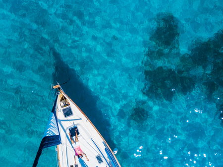 Aerial view to Yacht in deep blue sea. Drone photography Standard-Bild