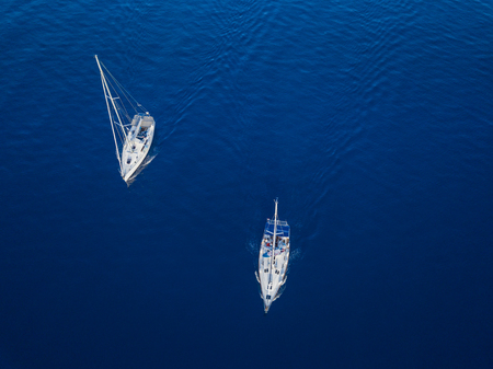 Aerial view to two Yachts in deep blue sea. Drone photography 免版税图像