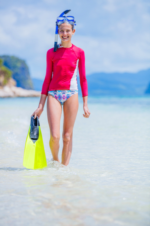 Teenage girl in bikini carrying scubadiving equipment Stockfoto