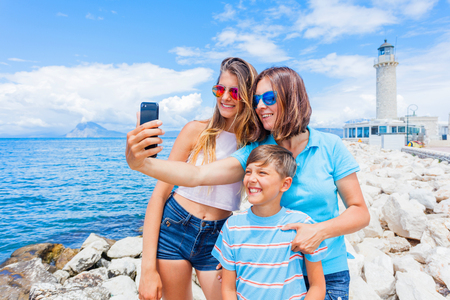 Happy family making selfie in front of Patras lighthouse, Peloponnese, Greece.
