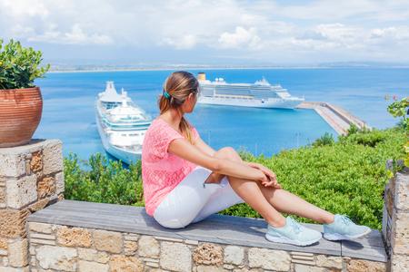 Teens girl looking at a cruise ship in the lagoon Mediterranean Sea, Greece