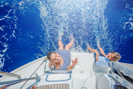 Boy with his sister on board of sailing yacht on summer cruise. Stock Photo