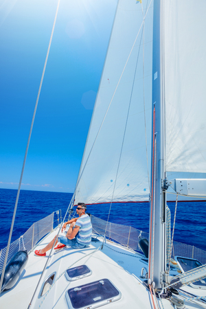 Young man sailing yacht. Holidays, people, travel Stock fotó